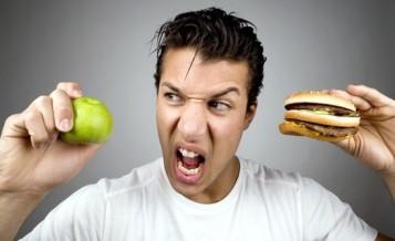 young-man-holding-apple-and-hamburger
